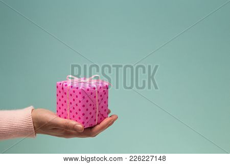 Female Hand Giving Pink Gift In Polka Dots