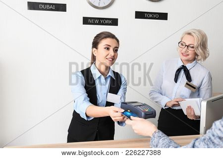 Female receptionist receiving payment for hotel room from client in hotel