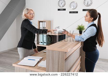 Female receptionist teaching trainee in hotel