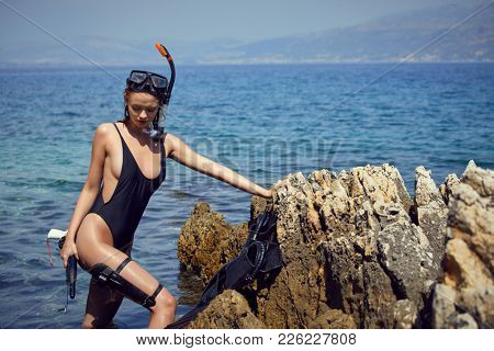 Young woman with a mask going to snorkel in clear sea