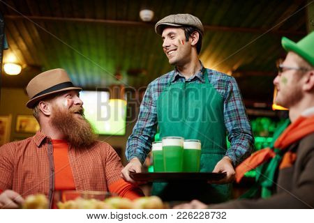 Happy waiter of irish pub bringing three glasses of beer on tray for bearded man and his friend