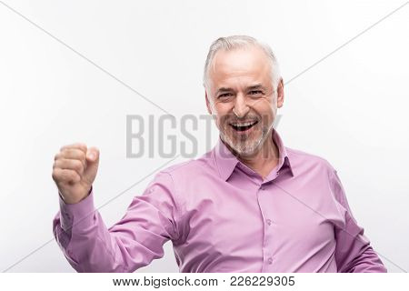 Well Done. Upbeat Young Man In A Lilac Shirt Clenching His Fist In Triumph And Smiling Happily While