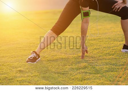 Young Asian Woman Runner Stretching Legs Before Run Outdoor Workout In The Park At Sunset. Exercise,