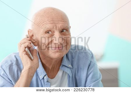 Hearing impaired man talking on phone at home