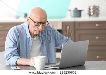 Hearing impaired man working with laptop at home
