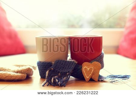 White And Red Mug Wrapped In A Blue Scarf And Two Cookies In The Form Of Hearts In The Background Of