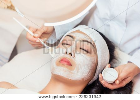 Close-up of the face of a young woman relaxing under the gentle touch of the specialist, applying on her cheeks white facial mask with rejuvenating effects
