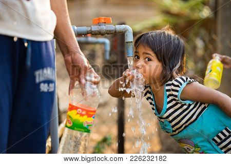 Kon Tum, Vietnam - Mar 29, 2016: A Little Girl Drink Water From Outdoor Tap Which Water Supplied By