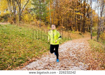 Young Athlete With Smartphone In Yellow Jacket Running Outside. Trail Runner Training For Cross Coun