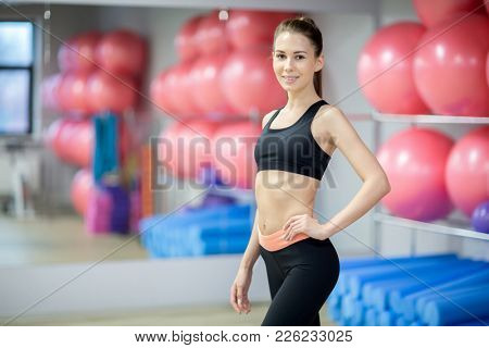 Fit young female in activewear keeping one hand on waist and looking at camera in gym