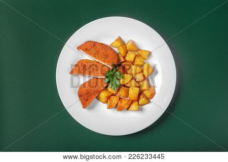 Schnitzel With Fried Potatoes On A White Plate On A Green Background. View From Above. Garnished Wit