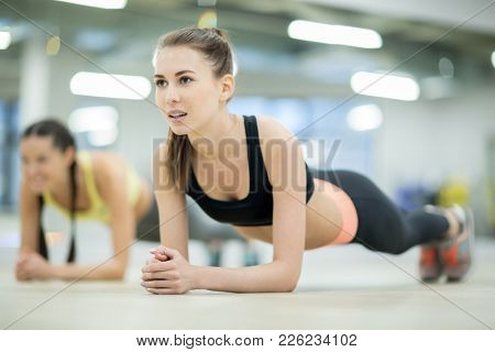 Active girls doing planks on the floor of fitness club or at leisure center