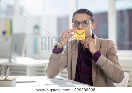 Young businessman in eyeglasses holding sticker with drawn smile by his mouth while looking at camera
