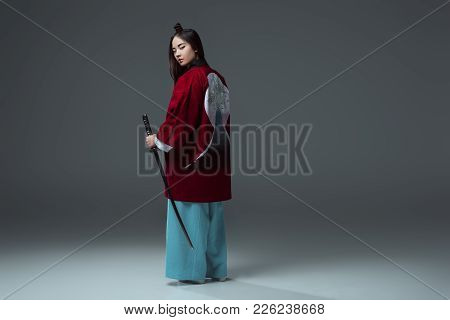 Back View Of Samurai In Kimono Holding Katana And Looking At Camera On Grey