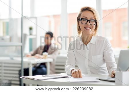 Happy middle aged businesswoman in eyeglasses sitting by her workplace in office and looking at camera with toothy smile