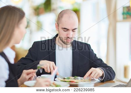 Businessman eating vegetable salad in restaurant during lunch break and talking to colleague