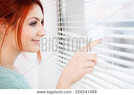 Close Up Of Woman Smiling At The Window While Looking Through The Jalousie