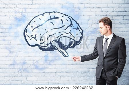 Handsome Caucasian Businessman Drawing Creative Brain Sketch On Brick Wall Background. Brain Storm A