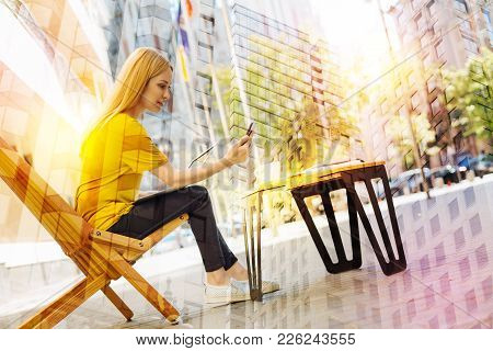 Reading Messages. Attentive Concentrated Young Woman Sitting Alone In A Beautiful Cafe And Feeling G