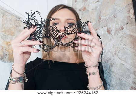Blonde Girl With Black Carnival Mask. Masquerade. Portrait Of Beautiful Blond Woman In A Carnival Ma