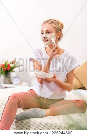 Attractive Woman Applying Clay Mask On Face While Sitting On Bed