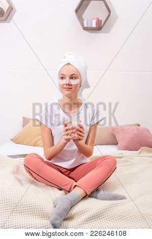 Beautiful Young Woman With Cosmetic Facial Patches With Glass Of Milkshake At Home
