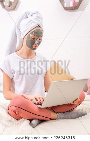 Young Woman With Cosmetic Clay Mask Working With Laptop At Home