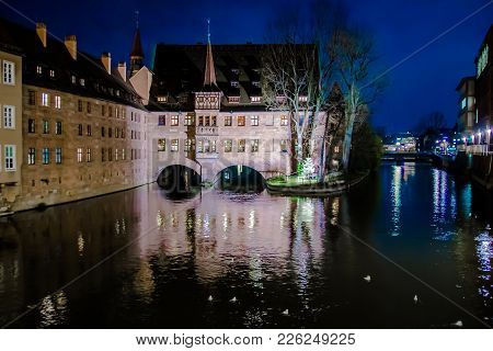 View Of The Heilig-geist-spital (hospice Of The Holy Spirit) At Night In The Old Town Of Nuremberg,