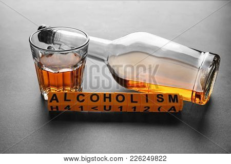 Bottle and glass of alcohol with word