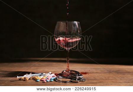 Composition with wine, drugs and handcuffs on table. Alcoholism and drug addiction