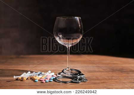Composition with wineglass, drugs and handcuffs on table. Alcoholism and drug addiction