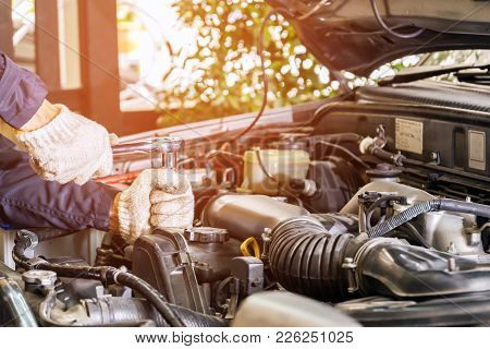 Car Repairman Wearing A Dark Blue Uniform Was Wrenching At The Engine Of A Car That Came Into Servic