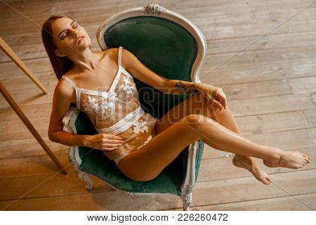 Beautiful Young Woman In White Lace Lingerie And Tank Top Sits In Armchair Against Background Of Woo