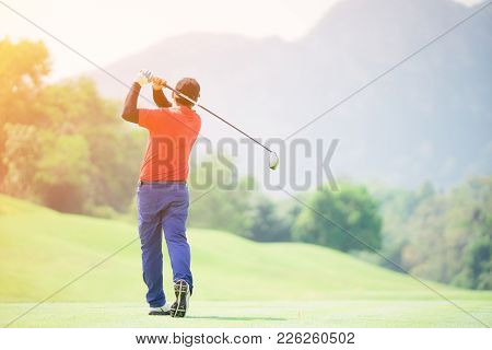 Golfer Hitting Golf Shot With Club On Course While On Summer Vacation,man Playing Golf On A Golf Cou