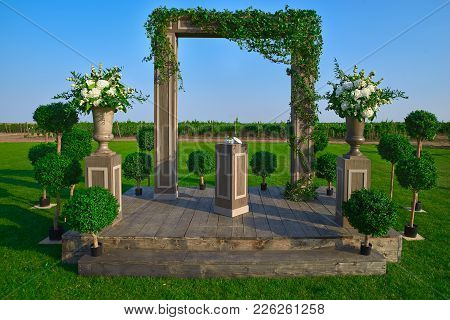 Wedding Arch Decorated With Flowers Outdoors. Beautiful Wedding Set Up. Wedding Ceremony On Green La