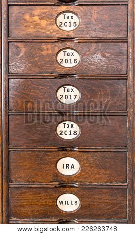 Wooden Drawers Of An Ancient Filing System With Labels For Income Tax Filing And Pensions