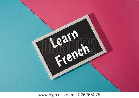 Learn French - Text On Chalkboard On Blue And Pink Bright Background.