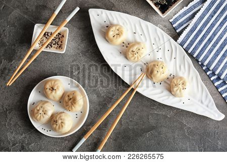 Plates with tasty baozi dumplings on table