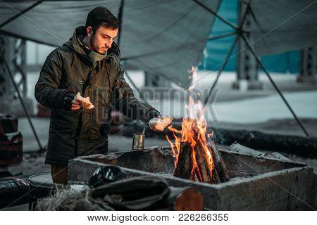 Stalker cooking food on fire, dog on background