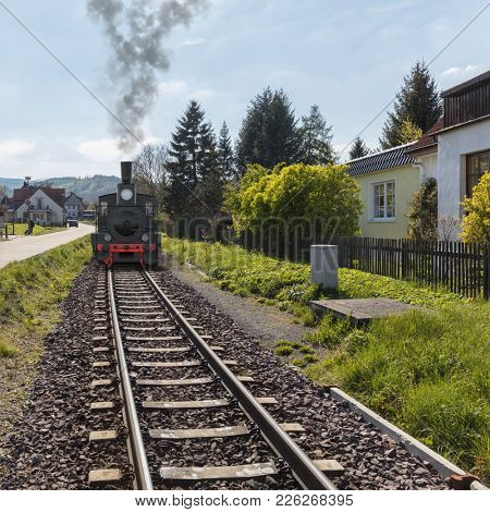 Railroad locomotive rides on rails in railway in spring