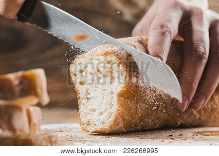 Whole Grain Bread Put On Kitchen Wood Plate With A Chef Holding Gold Knife For Cut. Fresh Bread On T