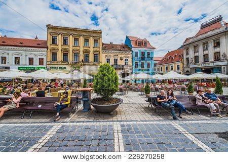 Brasov, Romania - July 5, 2016: People Sits On A Benches On The Council Square, Old Town Of Brasov