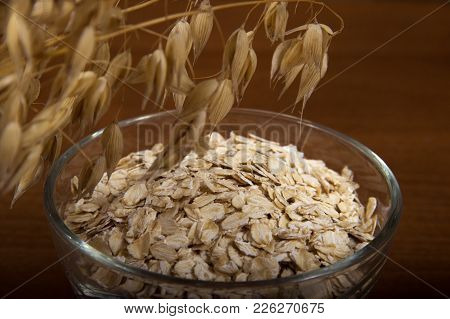 Oat Ears Stems And Oat Flakes In A Bowl On A Dark Brown Wood Background. Oatmeal Flakes Coarse. Larg