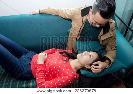 Beautiful Asian Girl Lie Down With Her Boyfriend In Sofa,happy Family Concept