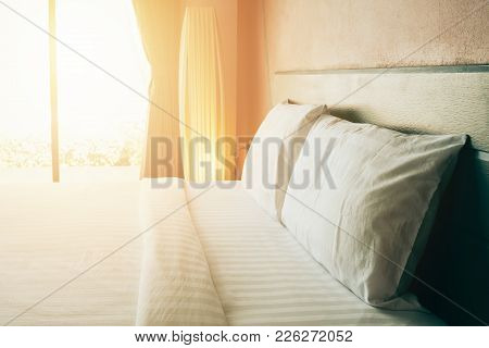 Maid Up Bedding In Bedroom With Sunrise Effect, Clean White Bedding Sheet And Pillows In Beauty Room