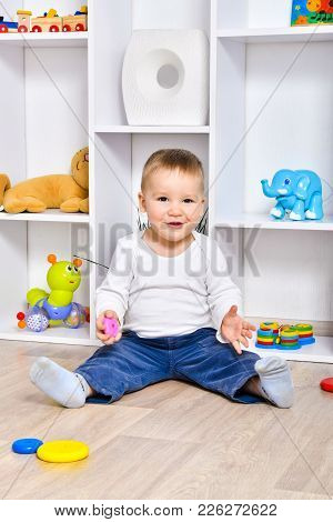 Happy Child Sitting On The Floor In The Playroom