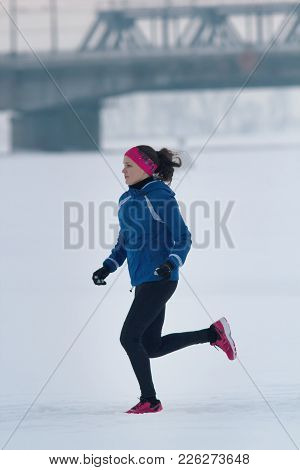 Young Female Athlete Running Diligently In Winter Through The Snow, Sport And Leisure Concept