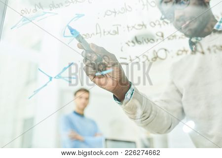 Portrait Of Two It Specialists Writing Formulas On Glass Wall In Modern Office, One Of Them African-