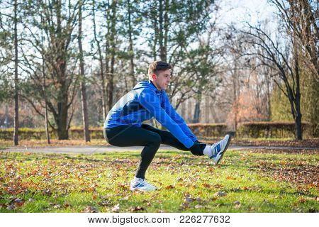 Young Male Runner Stretching in the Park in Cold Sunny Autumn Morning. Healthy Lifestyle and Active Sport Concept.