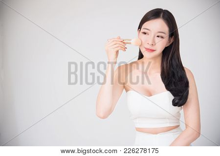 Asian Woman Using Cosmetics Makeup Blush On Face. Beauty, Makeup, Cosmetics Concept Isolated On Whit